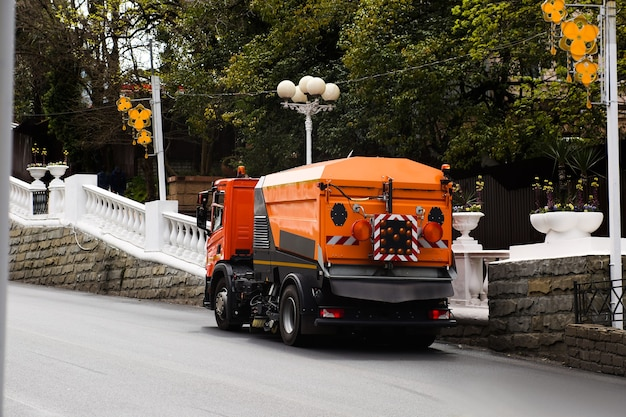 Cleaning machine washes asphalt road surface the city street.
