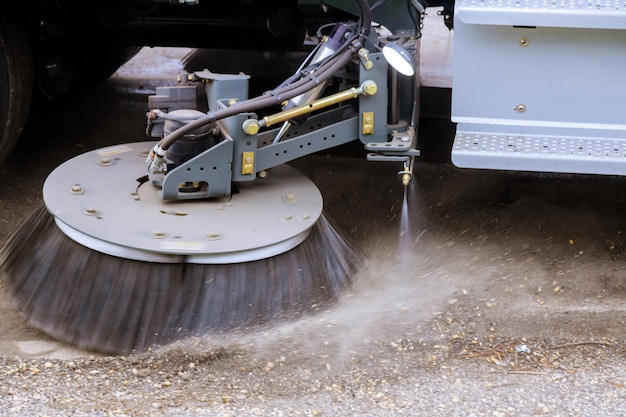 Cleaning machine washes asphalt road surface the street, of the town.
