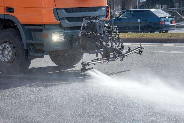 Машина чистки моет дорожное покрытие асфальта улицу города, конец вверх по взгляду.