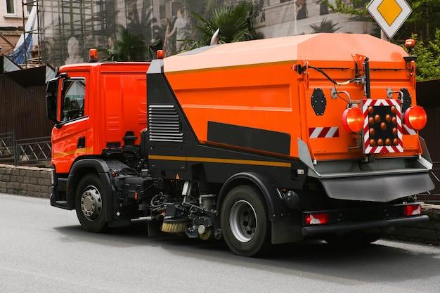 Уборочная машина моет асфальтовое покрытие дороги на улице города.