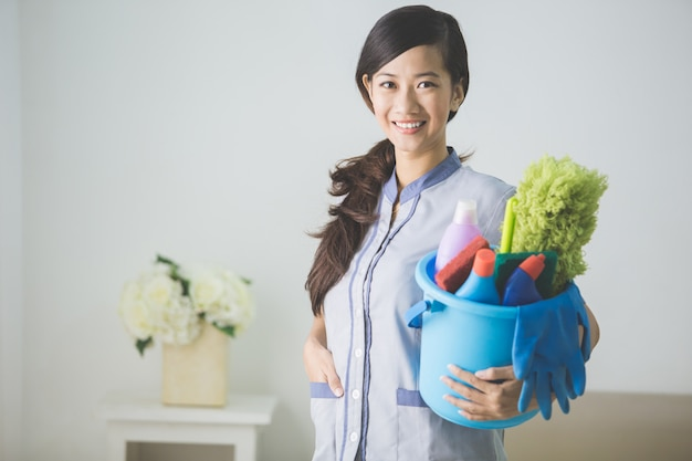 Cleaning maid woman smiling and holding a bucket with cleaning products