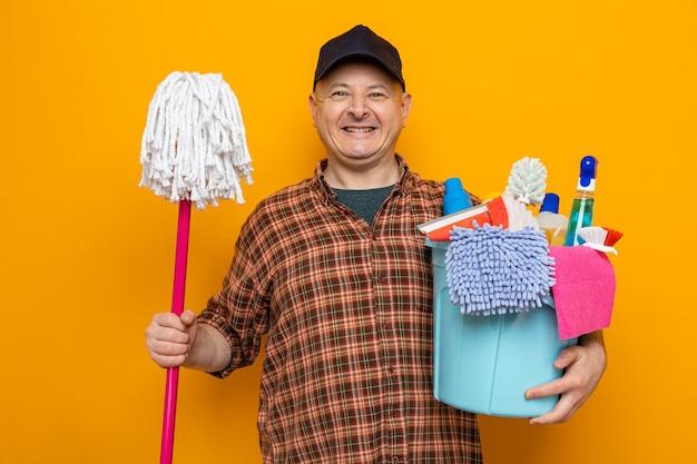 掃除道具とモップでバケツを保持している格子縞のシャツと帽子をかぶった掃除人は、広く掃除の準備ができて幸せで陽気な笑顔に見えます