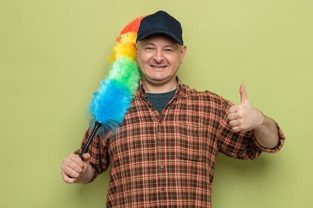 緑の背景の上に立って親指を元気に見せて元気に笑っているカメラを見てカラフルなダスターを保持している格子縞のシャツと帽子の男を掃除
