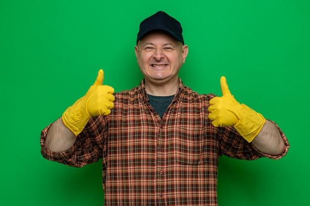 Уборщик в клетчатой рубашке и кепке в резиновых перчатках выглядит счастливым и веселым, показывает большие пальцы вверх и широко улыбается
