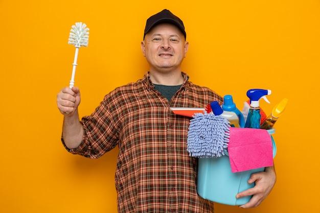 Uomo delle pulizie in camicia a quadri e berretto che tiene secchio con strumenti per la pulizia e spazzola per la pulizia che guarda l'obbiettivo sorridente fiducioso pronto per la pulizia in piedi su sfondo arancione
