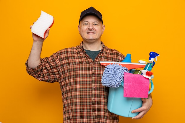 Cleaning man in plaid shirt and cap holding bucket with cleaning tools and sponge looking with smile on face