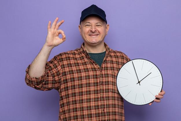 Uomo delle pulizie in camicia a quadri e berretto che tiene l'orologio guardando la telecamera sorridendo allegramente facendo segno ok felice e positivo in piedi su sfondo viola