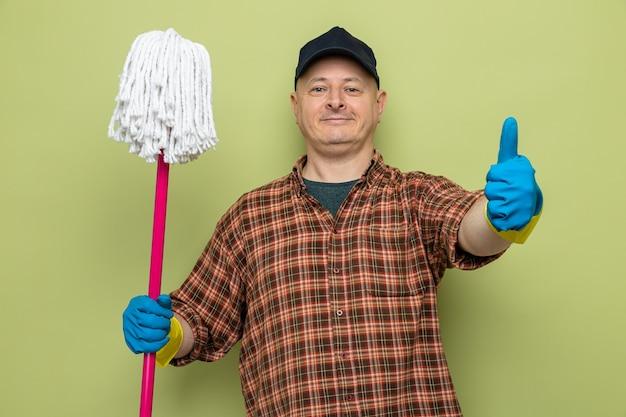 Uomo delle pulizie in camicia a quadri e berretto che indossa guanti di gomma che tengono mop guardando la telecamera con un sorriso fiducioso sul viso che mostra il pollice alzato in piedi su sfondo verde