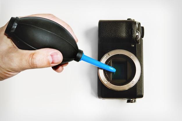 Уборка. рука мертвеца, держащая грушу для очистки пыли от камеры. обдув матрицы беззеркальной системной камерой.