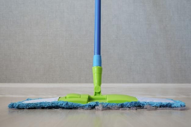 Чистящая швабра с пылью на деревянном полу спальни, вид спереди