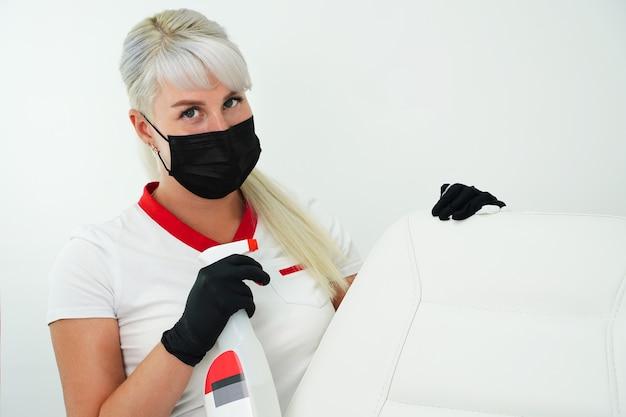 Уборка рабочего места в спа-салоне красоты молодая женщина в защитной маске и перчатках держит ...