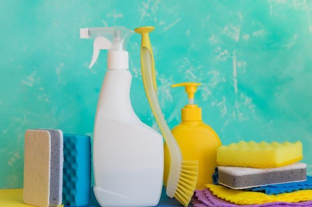Чистящие средства, бытовые, санитарные принадлежности. разнообразие красочных чистящих средств для дома на синем фоне. концепция уборки и генеральной уборки. бутылки с моющим средством, щеткой, губкой и перчатками