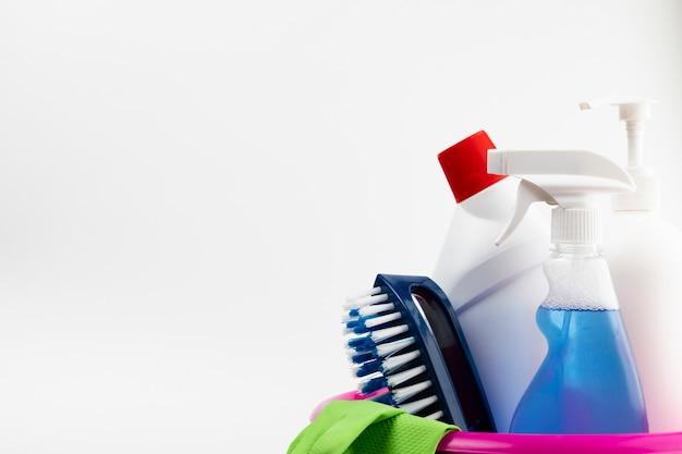 Чистящие средства и перчатки в розовом тазу