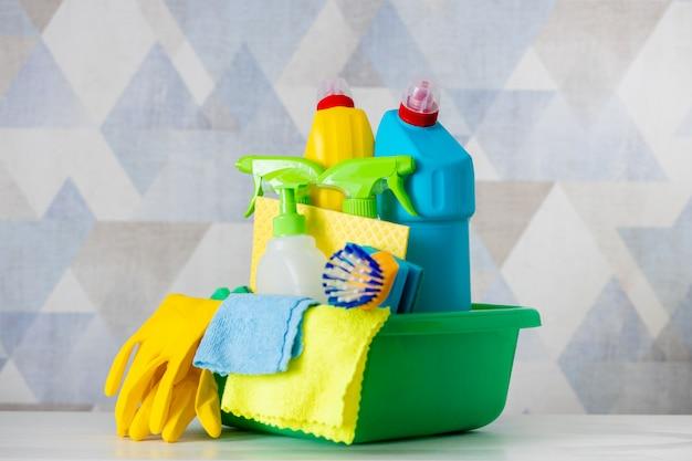 Чистящие средства и принадлежности в зеленой тазу - изолированные. ведро для уборки