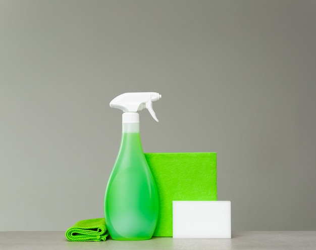 Cleaning products, green spray bottle with plastic dispenser, sponge and cloth for dust