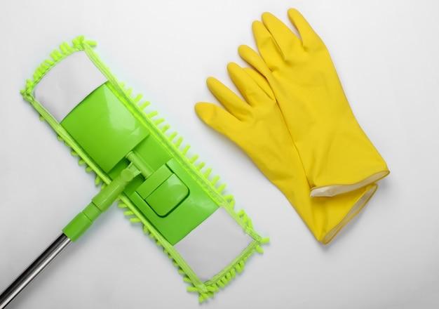 Чистящие средства. пластиковая зеленая швабра, перчатки на белой поверхности. дезинфекция и уборка в доме. вид сверху