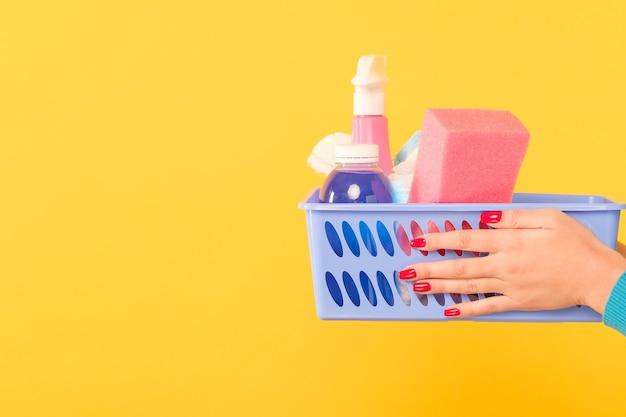 クリーニング製品の買い物。女性の手で物資のバスケット。黄色の背景にスペースをコピーします。