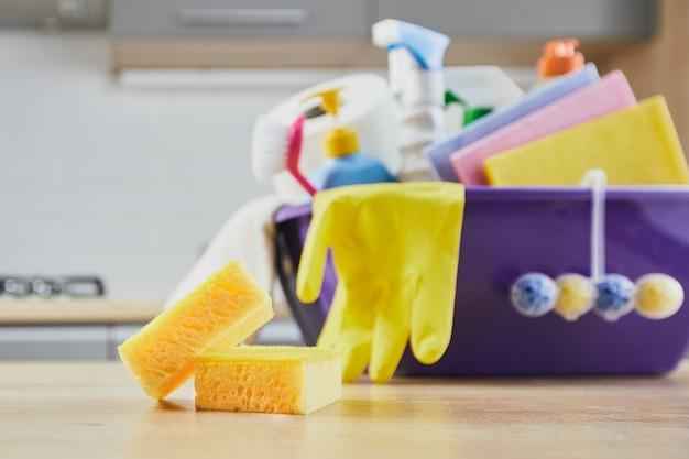 クリーニング製品:スポンジ、ボトル、黄色い手袋、ブラシ、テーブルへのスプレー、灰色のキッチンの背景