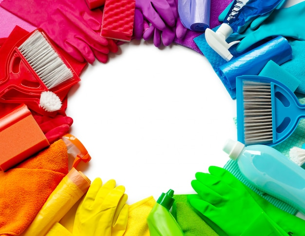 Cleaning products and tools different colors on white background. top view. circle copyspace in the middle.