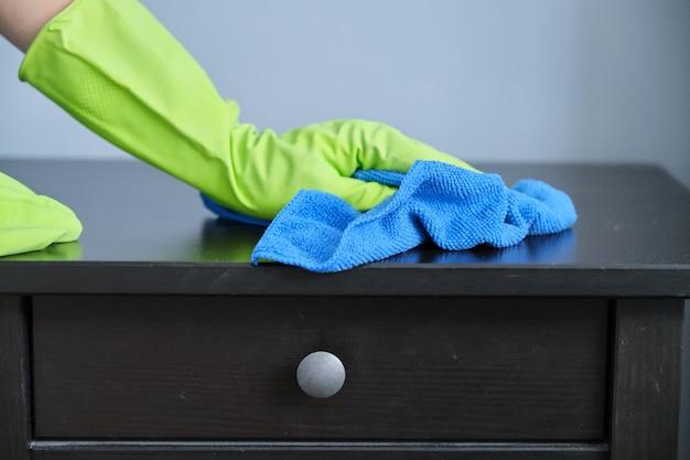 Услуги по уборке, крупный план рук в перчатках, вытирающих пыль салфеткой из микрофибры