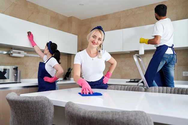 Команда службы уборки на работе на кухне в частном доме