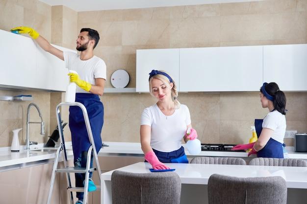 個人宅のキッチンで働く清掃サービスチーム