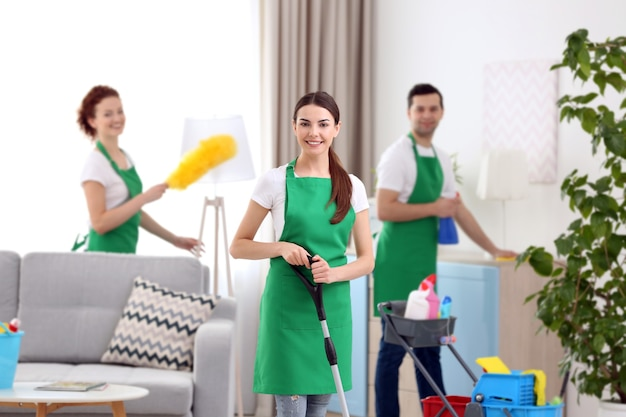 Cleaning service team working in living room
