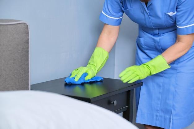 Уборка, женщина в униформе с перчатками с тряпкой в чистой комнате, уборка квартиры