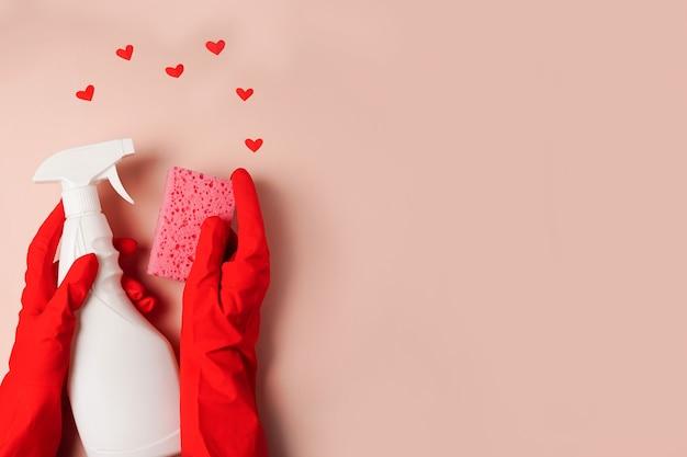 Рука работника службы уборки с белой бутылкой и сердечками на розовом