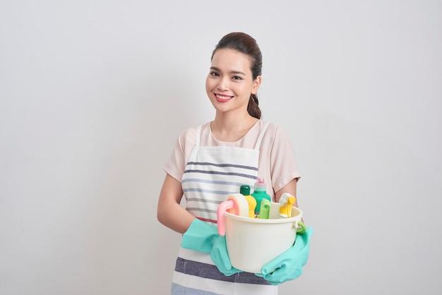 Концепция клининговых услуг. молодая жизнерадостная женщина, держащая ведро с моющими средствами и тряпками на белом изолированном фоне. бытовая и бытовая уборка