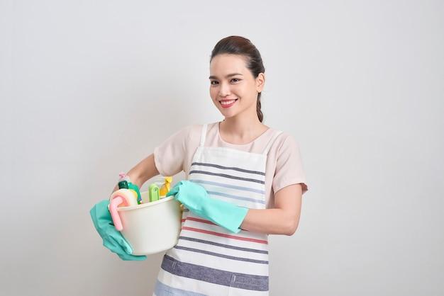 クリーニング サービスのコンセプト。孤立した白地に洗剤とぼろが入ったバケツを持った若い陽気な女性。ハウスクリーニングとハウスクリーニング
