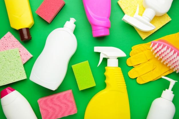 Набор для чистки. розовые и белые инструменты для чистки. чистящие средства, спрей, резиновые перчатки на зеленом фоне. flat lay
