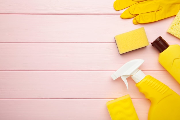 Набор для чистки. желтые инструменты для чистки. чистящие средства, спрей, резиновые перчатки на розовом деревянном фоне. flat lay