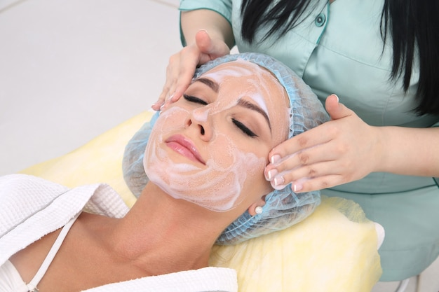 Cleaning the skin with foam, a beautiful woman in the beauty salon beauty