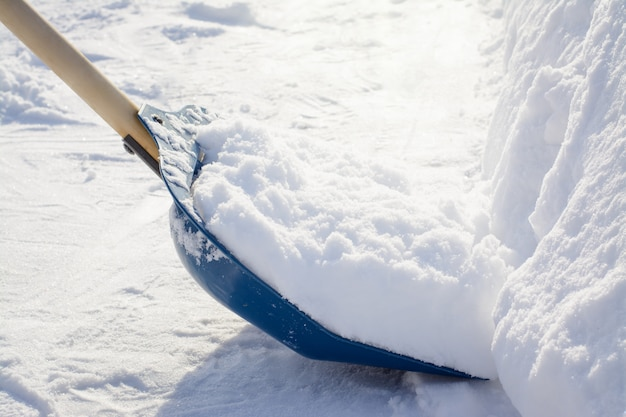 Cleaning snow with a shovel in the countryside after a heavy snowfall