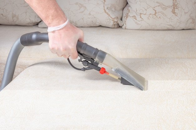 Cleaning the sofa with a vacuum cleaner