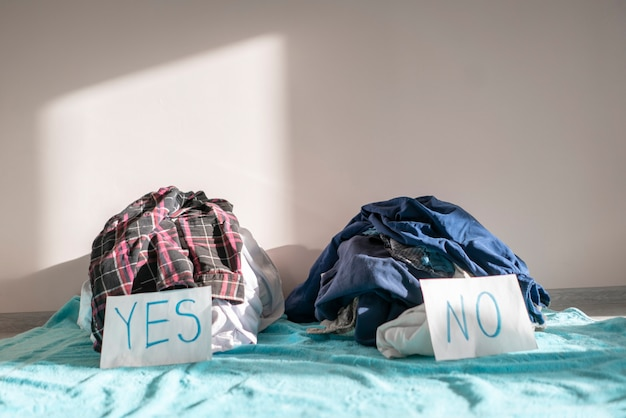A cleaning and sorting the clothes two heap of textile choose yes or no