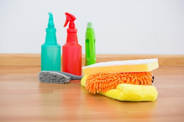 Cleaning sponge and chemical bottles on hardwood floor