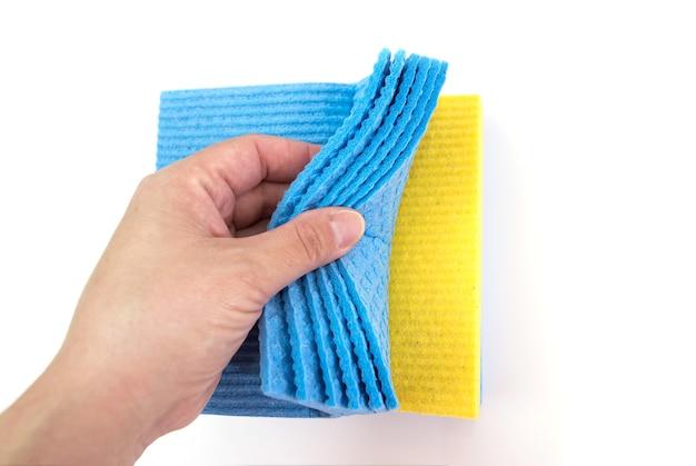집안의 청결을 유지하면서 흰색 표면에 손에 스폰지를 청소하십시오. 확대.