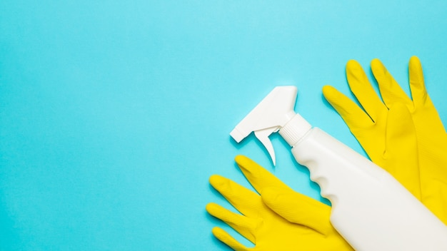 A cleaning spray lies on a yellow  latex gloves on a blue background, top view, copy space. cleaning supplies.