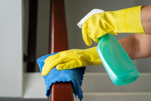 アルコールスプレーで階段手すりを掃除する