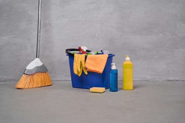 Чистящие средства. метла и пластиковое ведро или корзина с моющими средствами, бутылки с моющими средствами, стоящие на полу у серой стены. работа по дому, уборка, концепция домашнего хозяйства. дезинфекция