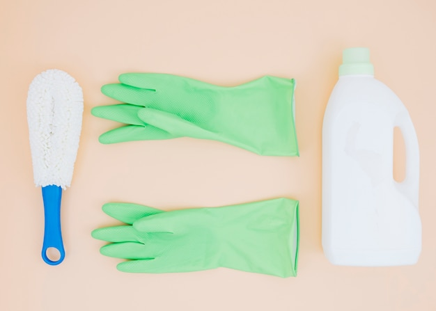 Cleaning supplies like brush; green gloves and detergent can on peach backdrop
