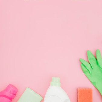 Cleaning supplies on pink background