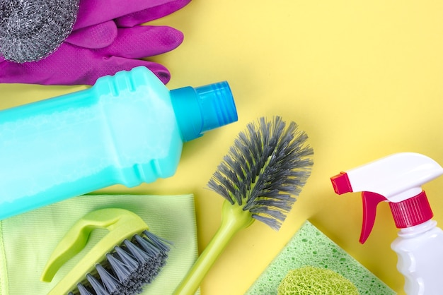 Cleaning supplies over yellow background