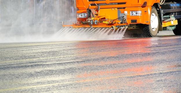 Подметально-уборочная машина моет асфальтовую дорогу распыляемой водой