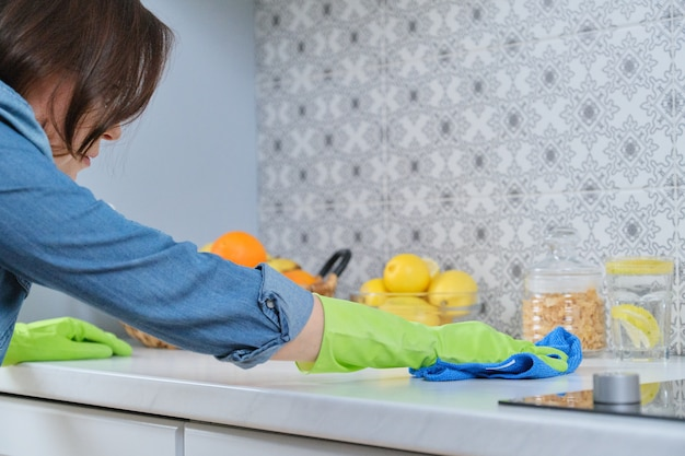 Cleaning table in kitchen after cooking, woman in gloves with rag cleans kitchen worktop
