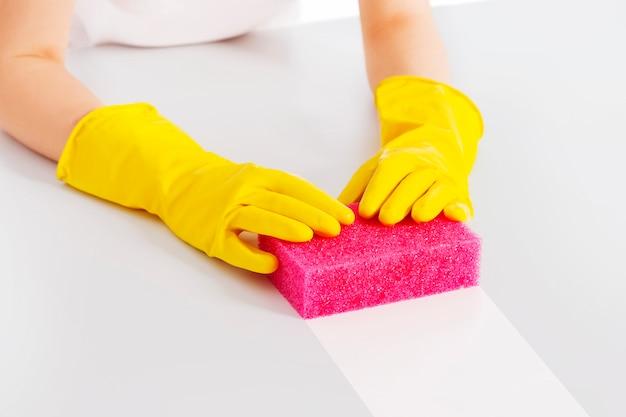 ピンクのスポンジと保護手袋でテーブルを掃除