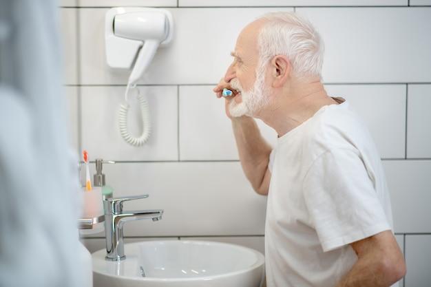 歯のクリーニング。彼の歯を掃除する白いtシャツの白髪の男
