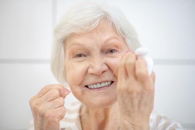 歯のクリーニング。白髪の女性が歯を掃除し、デンタルフロスを使用しています